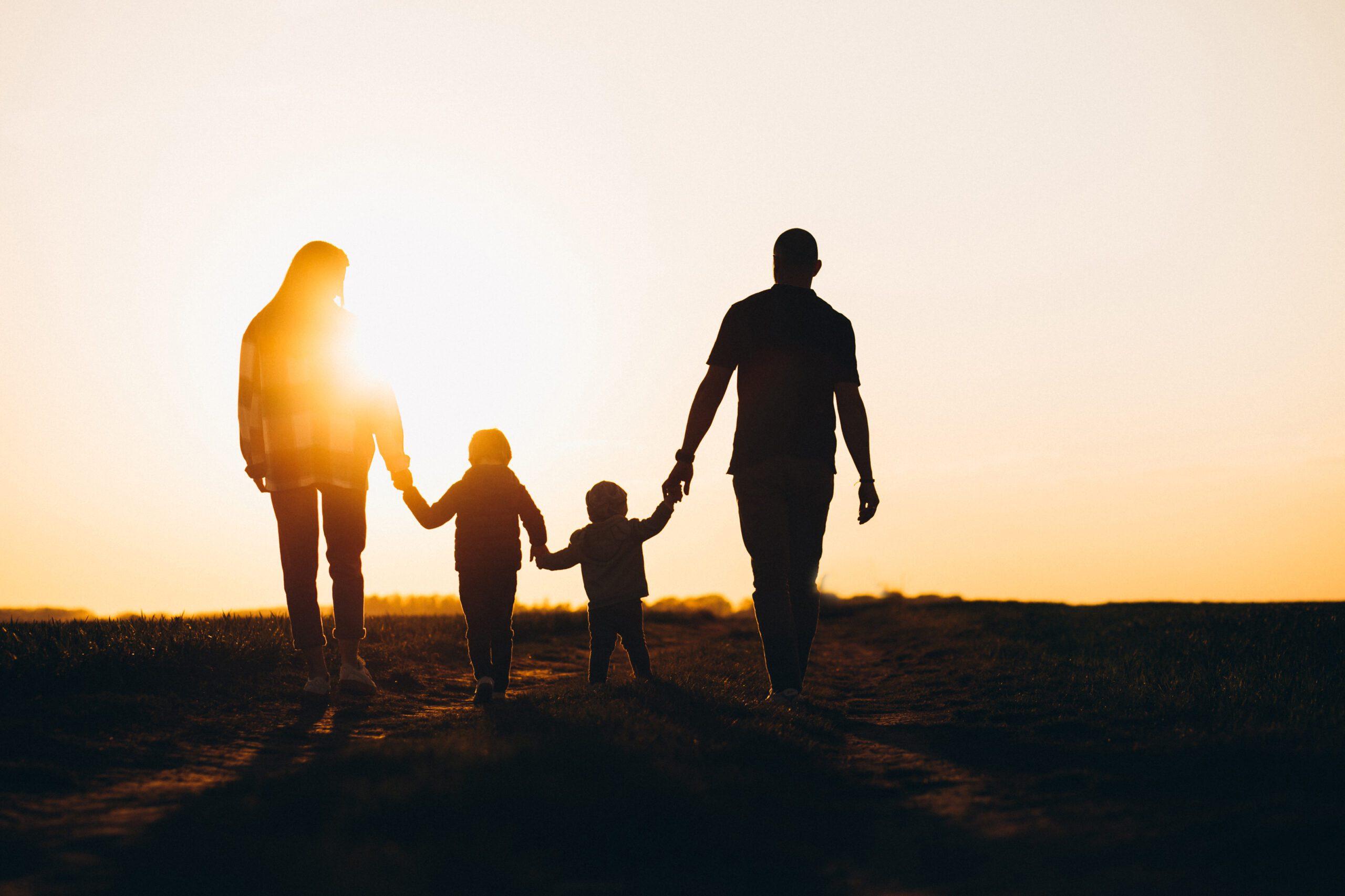 Família Feliz caminhando em direção ao por do sol de mãos dadas